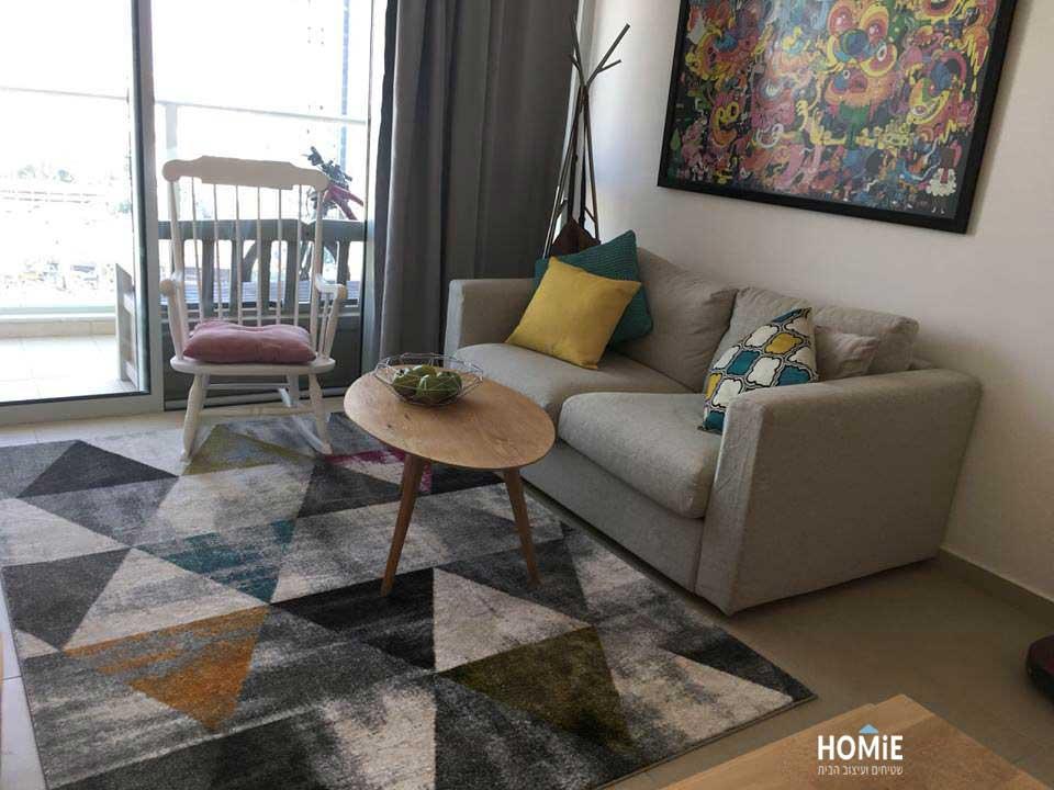 שטיח מעויינים-משולשים צבעוניים בסלון של לקוחה