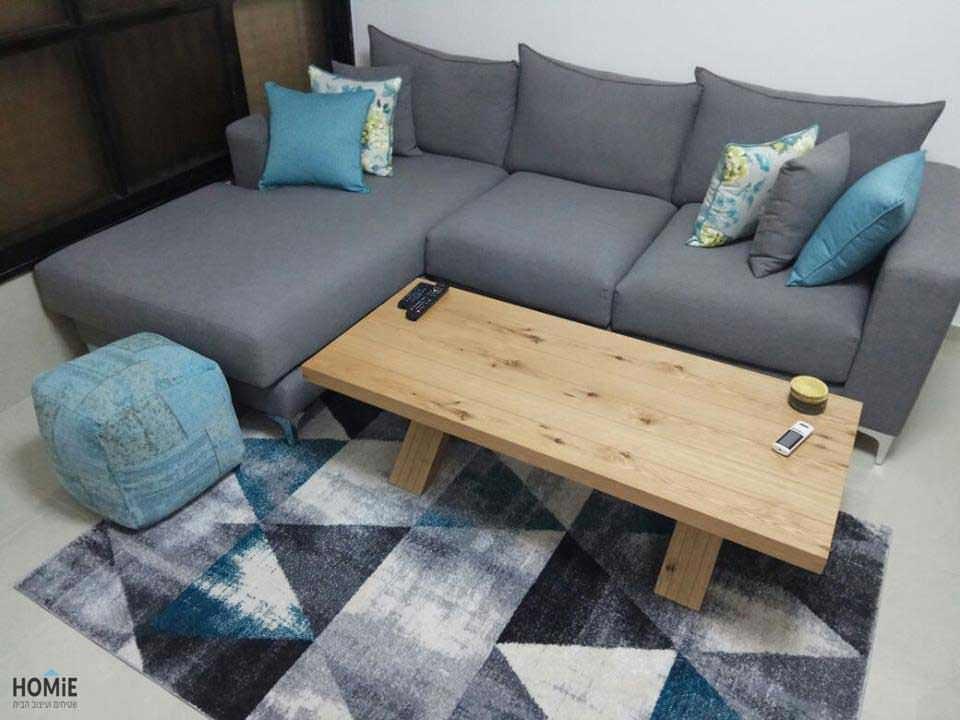 שטיח גיאומטרי, כריות נוי ופופים בסלון של טופז